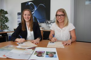 The Ziehl-Abegg apprentices Jennifer Zürn (left) and Marlen Geißler sign the sponsorship for two children in Swaziland